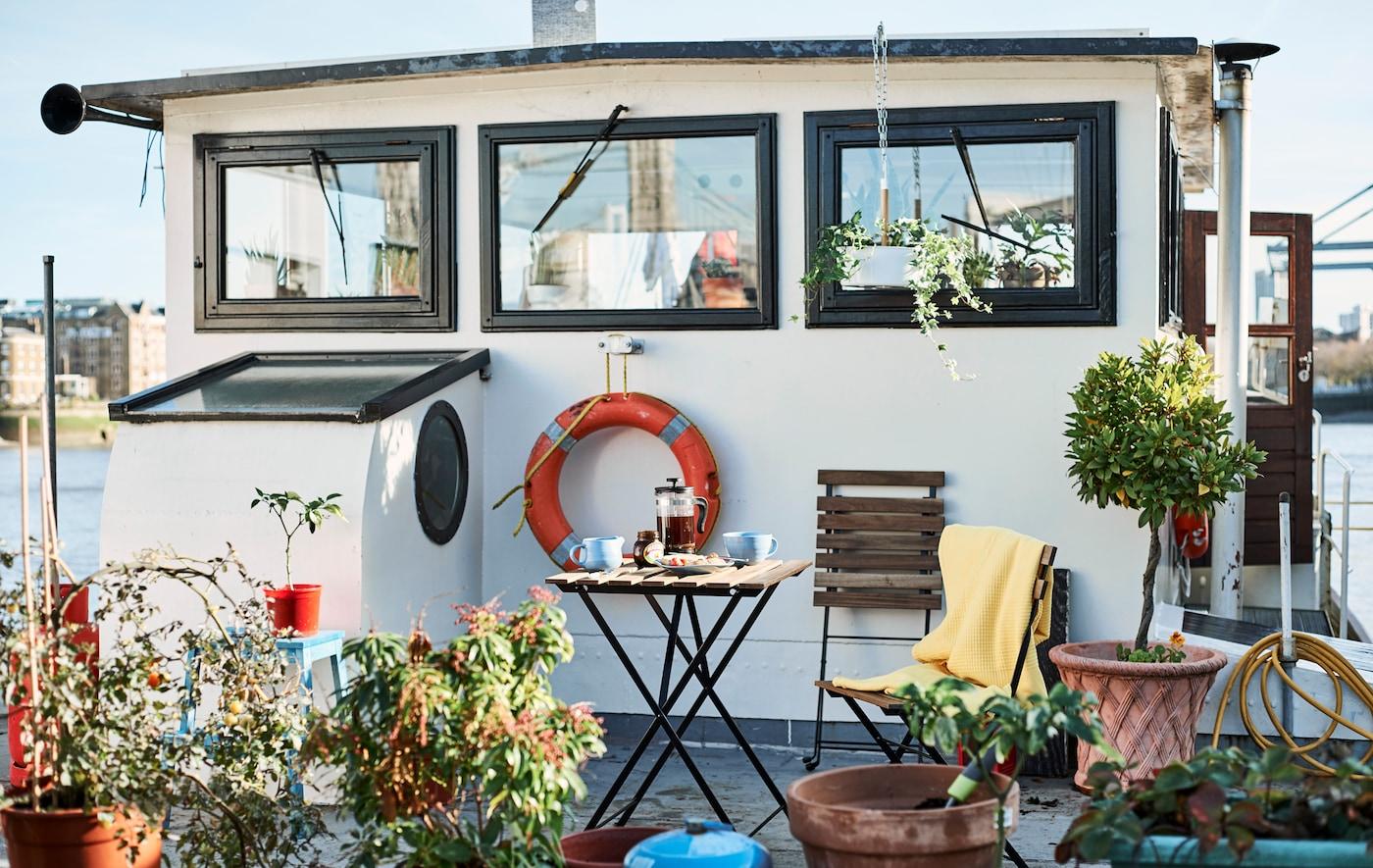 装点着户外植物的船屋,甲板上还放置着座椅。