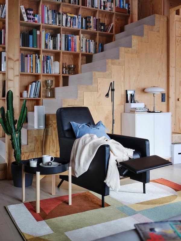 装饰着木墙的房间里有一把盖着毯子的黑色GISTAD 基斯塔 躺椅,椅子的脚踏有一定地斜度外倾着。