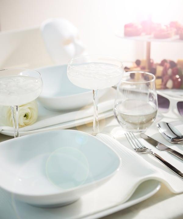 桌边面对面设有两个座位,餐桌以节庆风格布置,放有两个盘子、香槟杯和装饰品。