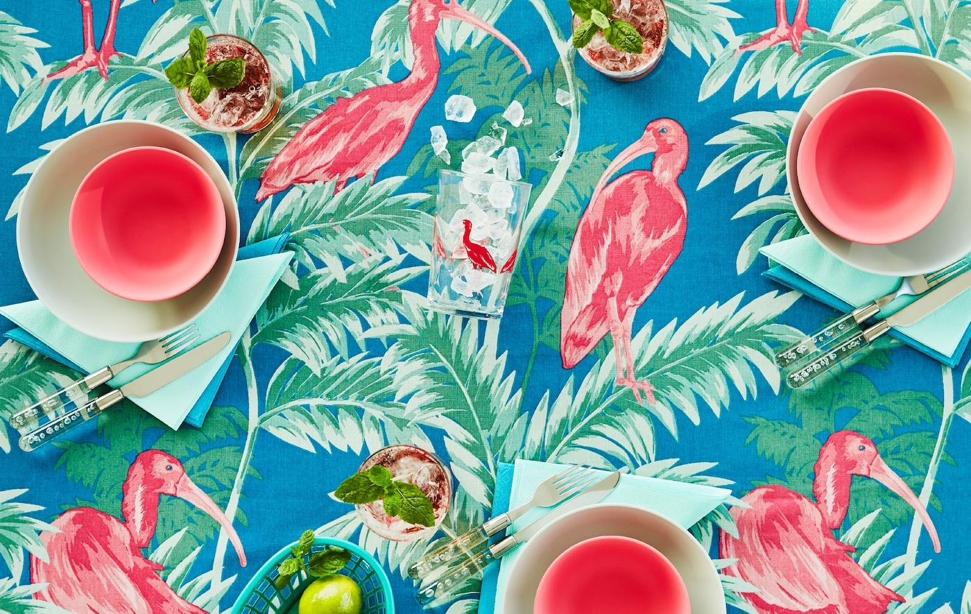 桌面上铺着饰有粉色、绿色和蓝色热带图案的桌布。桌子上摆着配套的餐具。
