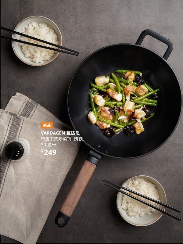 桌子上放着一个胡桃木柄的 VARDAGEN 瓦达恩 铸铁炒锅,锅里是刚刚炒完的芦笋和虾仁。旁边放着两碗米饭,上面摆着筷子。