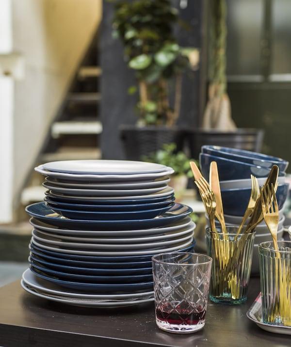 桌子上放着一摞盘子、刀叉和杯子。