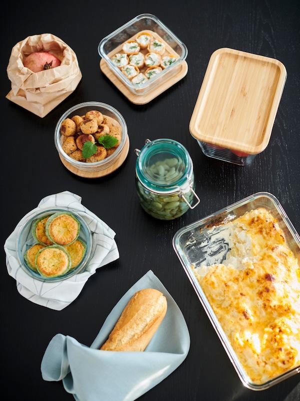 桌子一角放着各种罐子、一个烤盘和几个 IKEA 365+ 食品盒,均装满了不同菜肴。