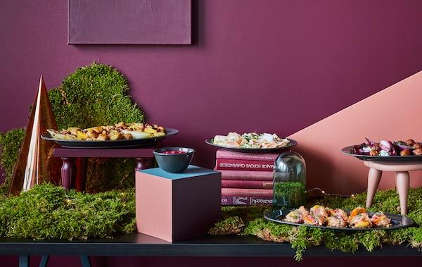 自助餐桌上摆放着各种食物、绿色植物以及一些深红色和绿色的装饰品。